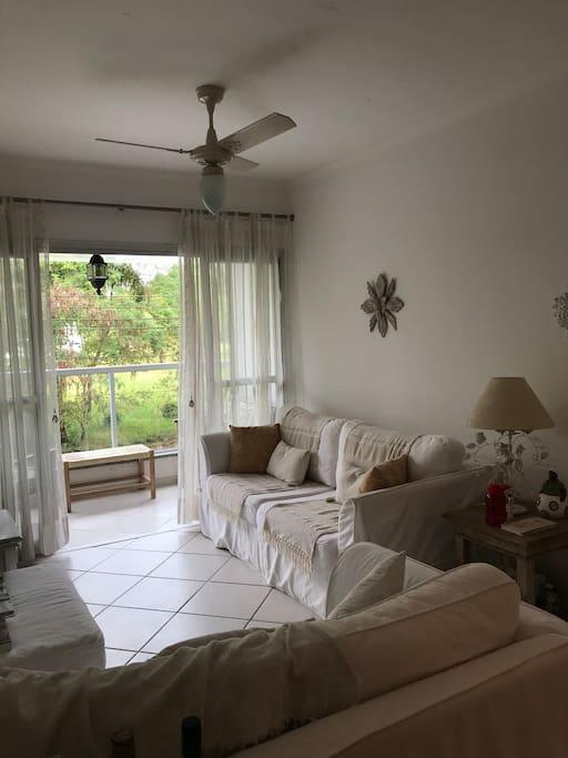 Sala de estar e TV. Aconchegante, cores claras. Privacidade total, não tem prédios na frente.