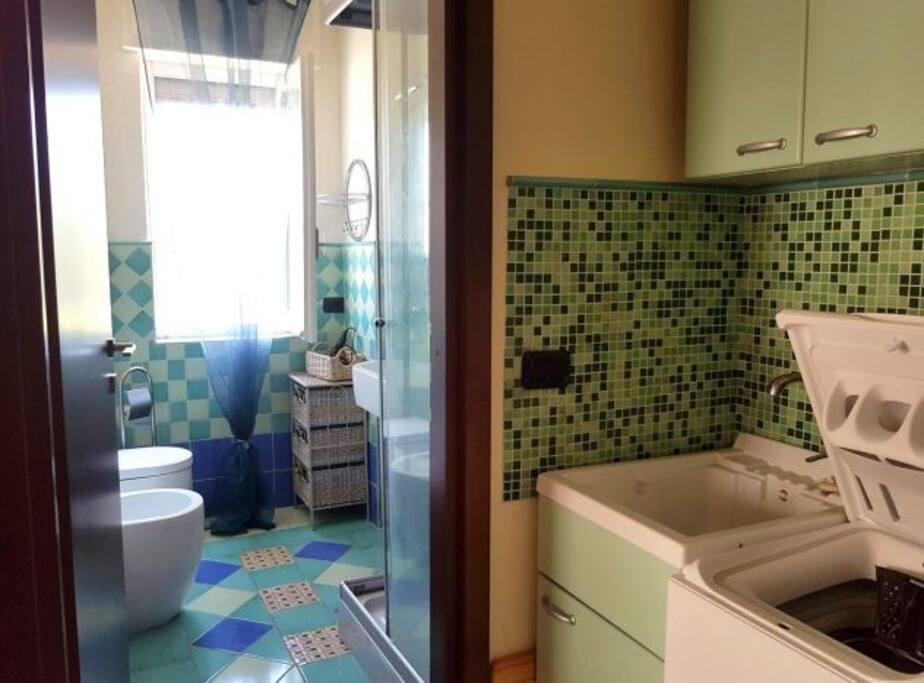 Bagno con box doccia, idromassaggio e radio. Antibagno con lavabo e lavatrice