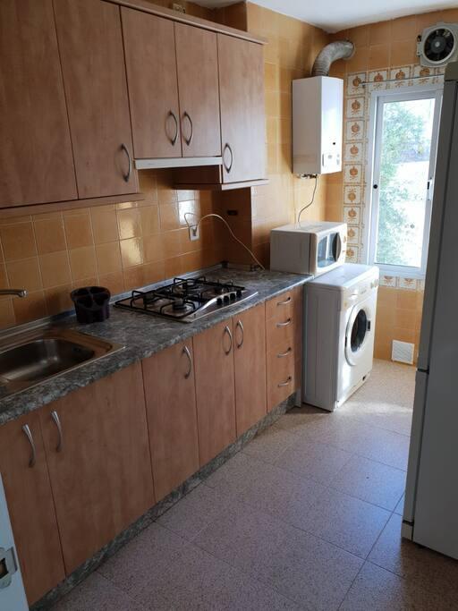cocina equipada con lavadora, nevera y microondas