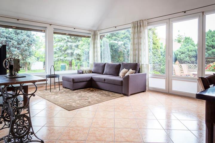 Sercem domu jest duży, jasny salon z wyjściem na prywatny taras. Okna posiadają rolety. Na rozkładanej kanapie spać mogą 2 osoby. Możliwa dostawka jednoosobowa.
