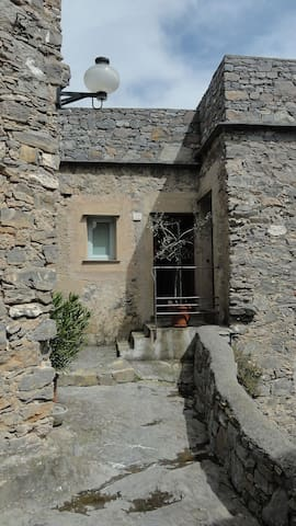 the entrance overlooks the rocky alleys and is located on a small stone podium, characteristic of many apartments in the village.