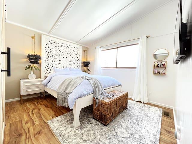 BR 2: Boho-themed room w/ a queen size Anthropologie Lombok bed, 42-in Sony LED TV, Barn door closet, luggage rack, wall hooks, door hooks, toiletry shelf, full-size mirror next to the door, Google Nest speaker, wall fan, steamer.