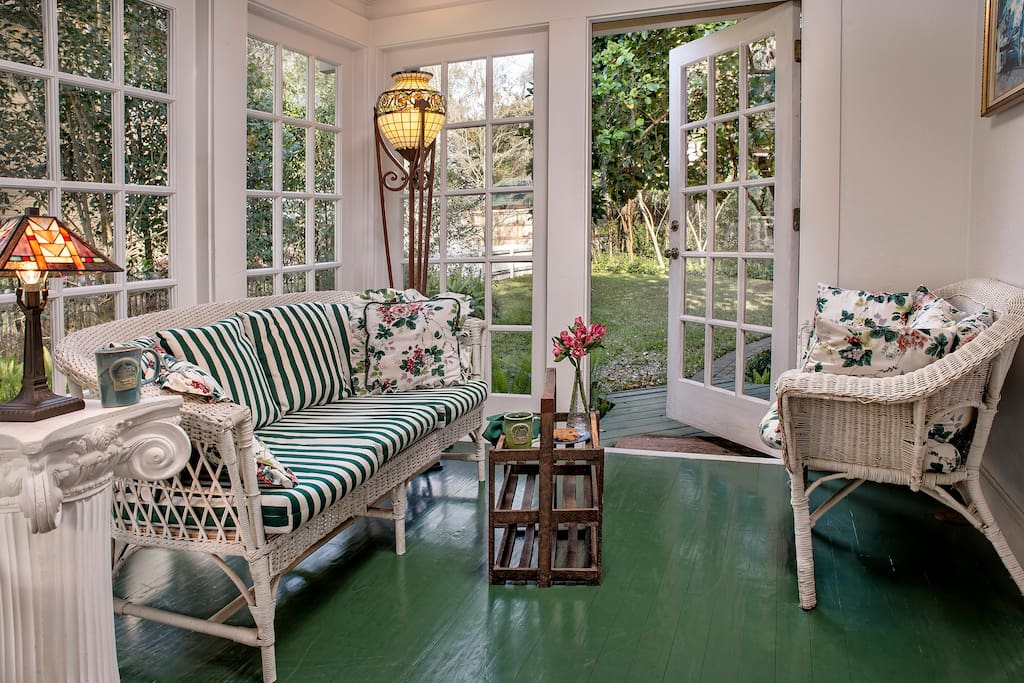 Beautiful and bright sunroom with seating and a dining room table.