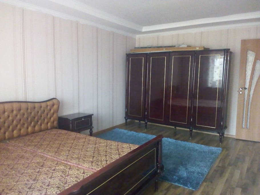 Bedroom with queen bed, wardrobe and balcny