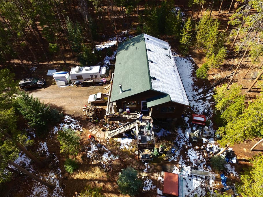 Drone photography of house showing surroundings and a bit of the forest & motor home