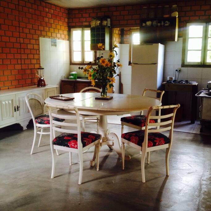 Sala de jantar e refeições integrada a cozinha com cook top e fogão a lenha