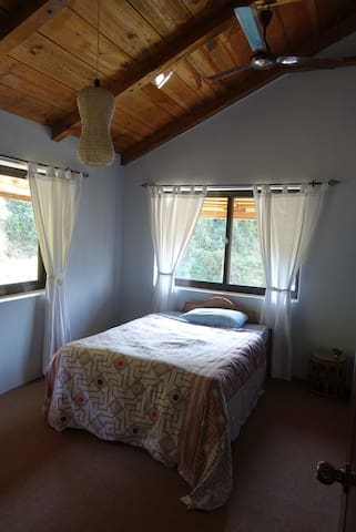 Guest bedroom with views to the backyard pool and rice paddy fields.
