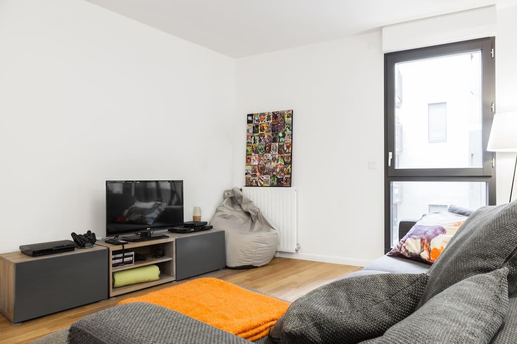 Salon lumineux et contemporain, canapé moelleux, ouvrant sur un balcon ensoleillé et une cour intérieure calme