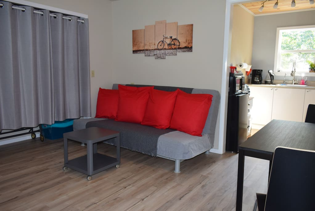 Living room with dining area overlooking the garden patio. Full size sofa bed. Twin roll-away bed and clean sheets in the closet by request.
