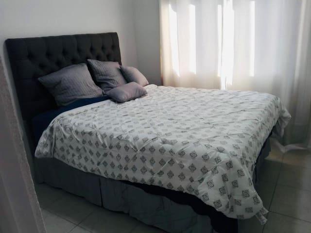 Cama queen size para dormitorio principal, espacio amplio con cortinas protectoras de luz para dar claridad y privacidad.