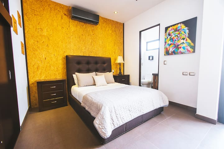 The final upstairs room has a queen bed and its own private bathroom with trendy particle board wall on one side, and a private full bathroom.