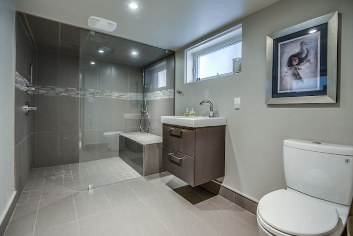 The bathroom is steps away. It has a rain shower head and a big bench