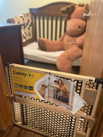 Toddler bedroom includes safety gate, changing pad, dresser, crib size mattress bed, toys, books, highchair, knotty stool, big moose, and more!