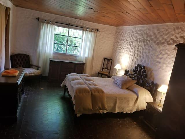 Amplio dormitorio cama matrimonial en suite con chimenea