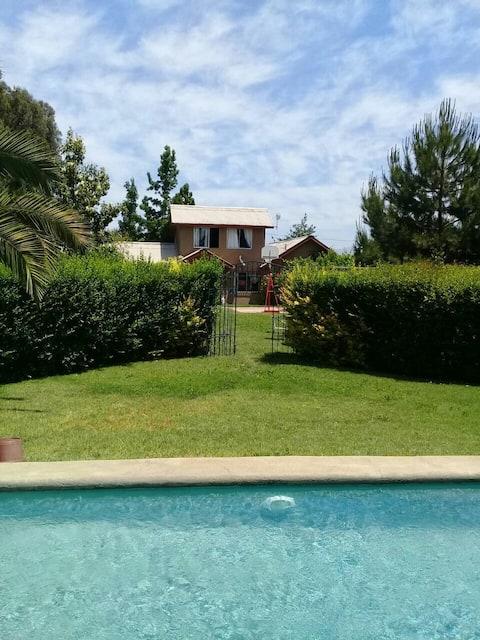 Casa con hermoso jardín y piscina.