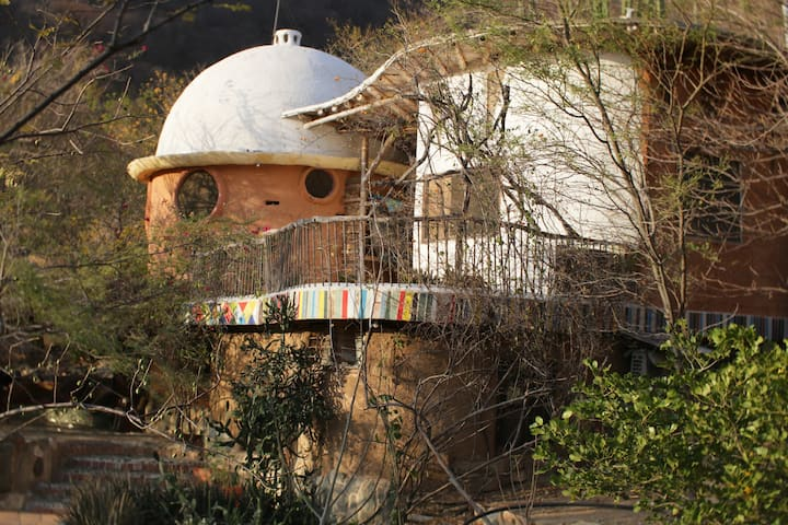 Hand built clay house nested in Taganga's woodland