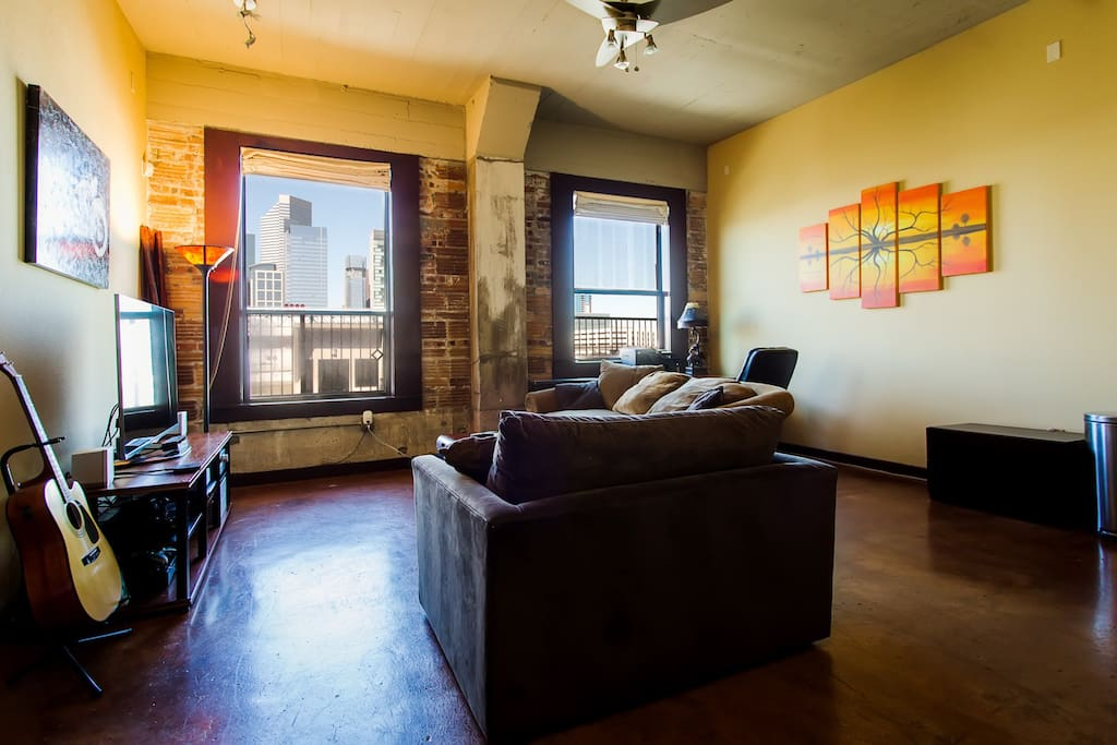Spacious living room with exposed brick, high ceilings, concrete floors, and an incredible view of downtown Houston.