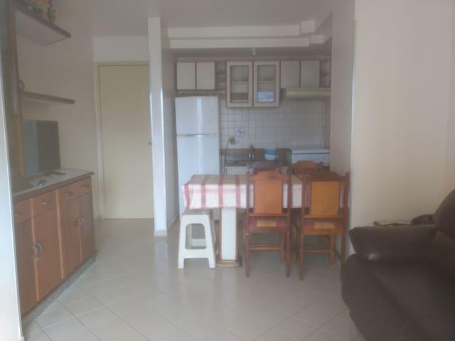 cozinha completa, mesa com 4 cadeiras. Sala com TV, sofá-cama e ventilador