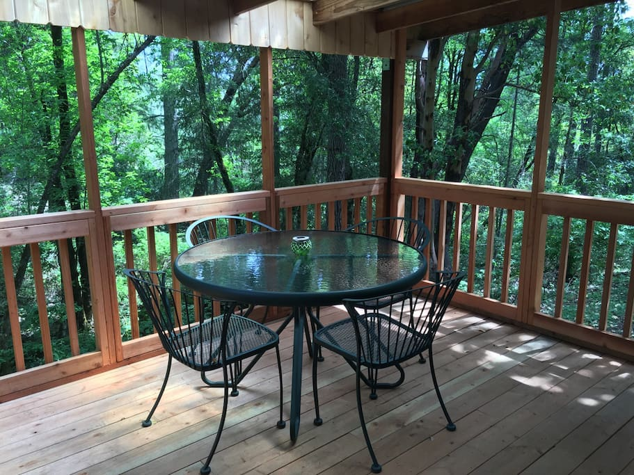 The renovated screened-in deck on the front porch of the cabin, overlooking the creek