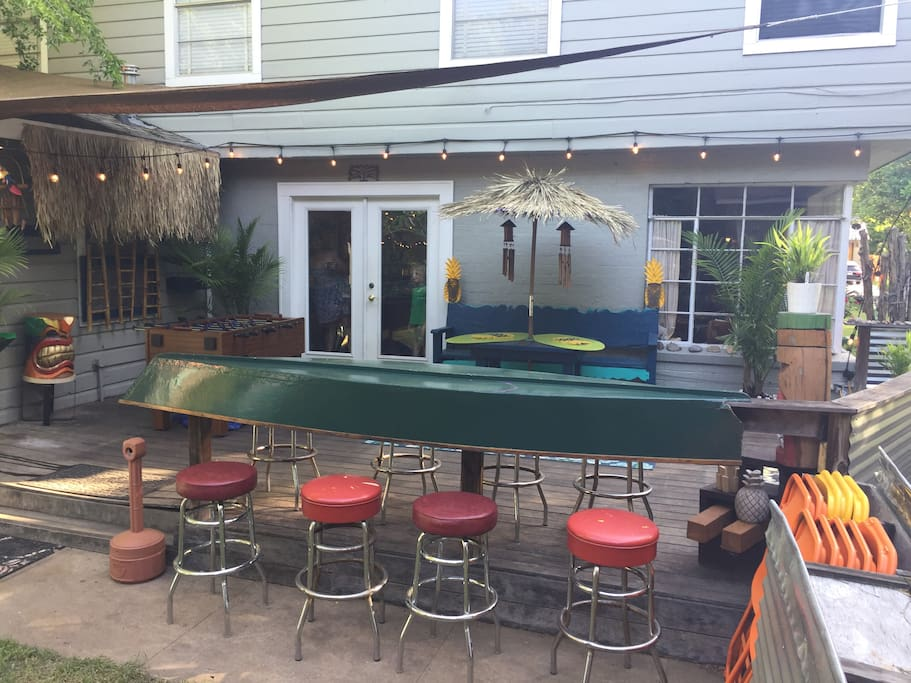 yard to deck view with cool canoe bar and bar stools  Tiki cups and hawaiian shirts for photos or your pinterest interests.
