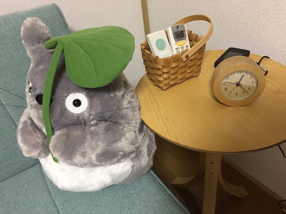Totoro holding a leaf as an umbrella, sitting on the sofa next to the coffee table