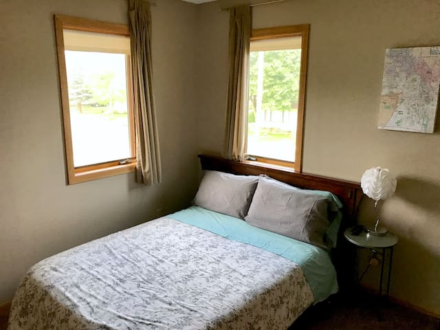 Guest room with a full size bed, closet, TV, fan, extra pillow and blanket, and a full size mirror.
