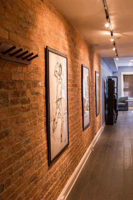 Long hallway with exposed brick and original artwork.