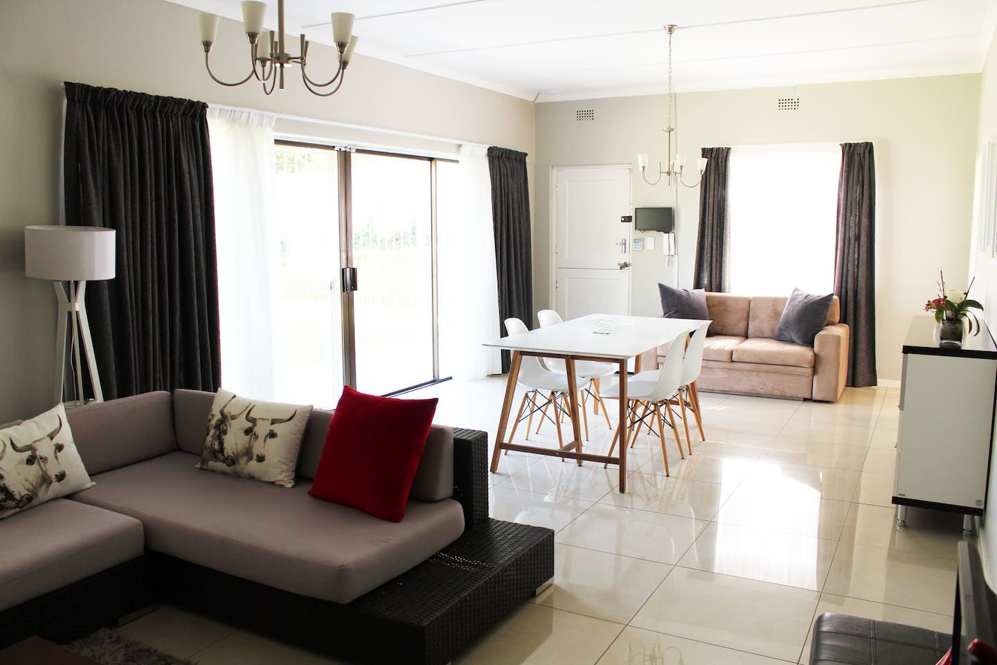 Secure Modern open plan TV room and dinning room with sliding doors to garden, pool and play area. ( Electric fence, CCTV, alarm and panic button.)