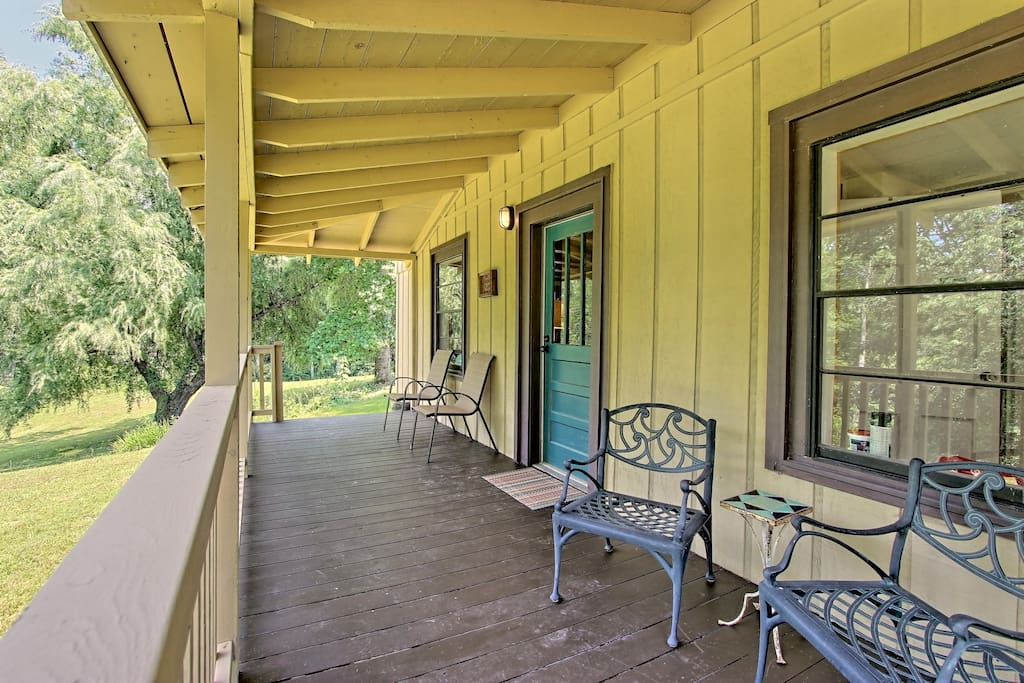 The front porch overlooks the expansive property and lush forestry.
