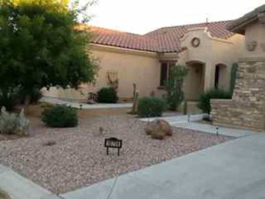 House exterior has beautiful desert landscaping, and trees.