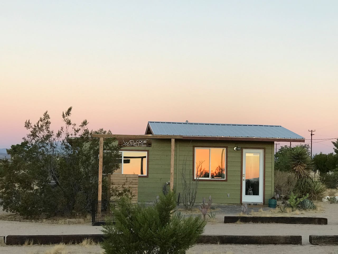 MOJAVE GREEN cabin at sunrise. Railroad ties line the driveway and a pathway leads up to the front door where you access the cabin with a door code.