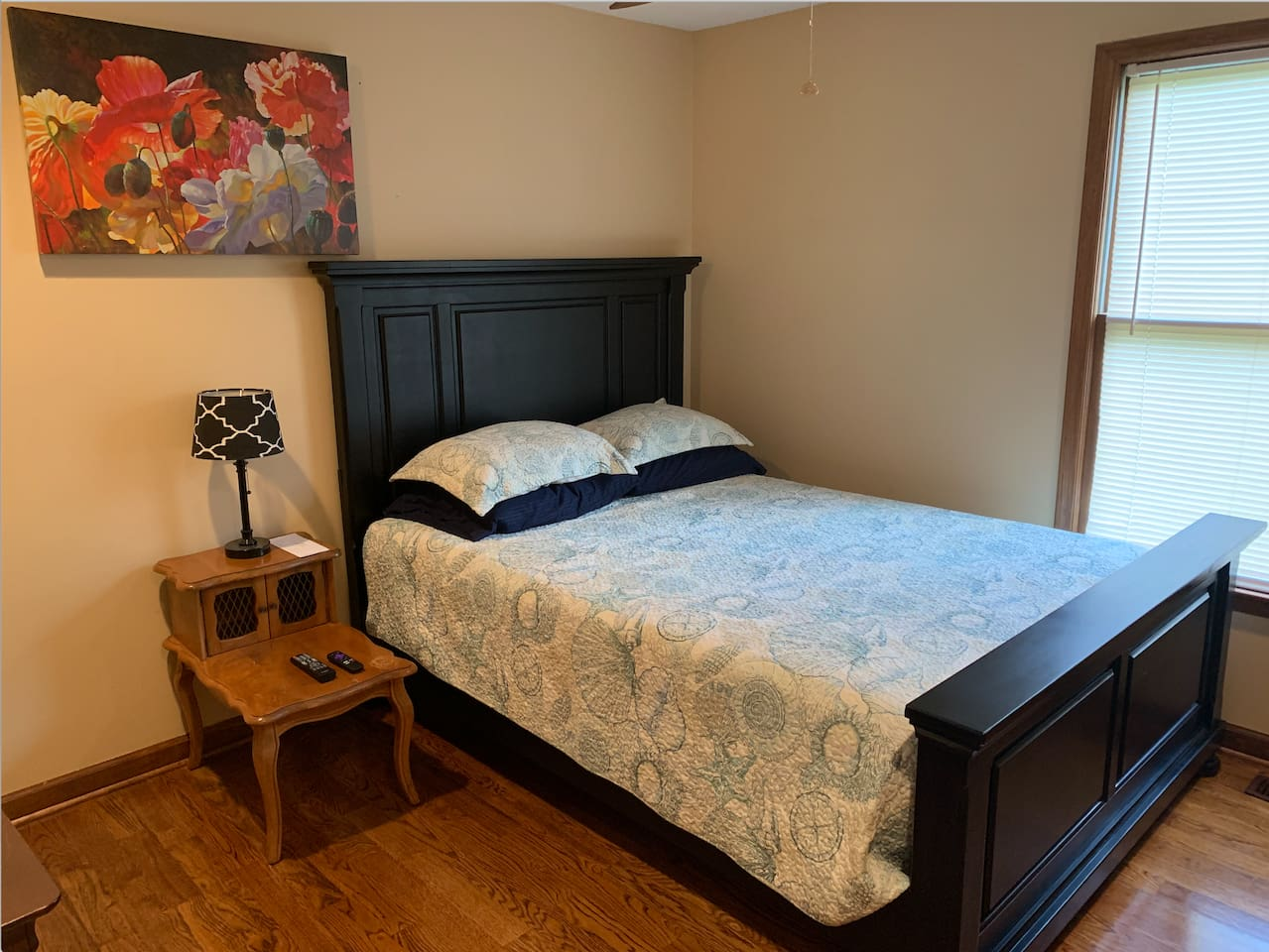 Spacious queen size bed in a bright room.
