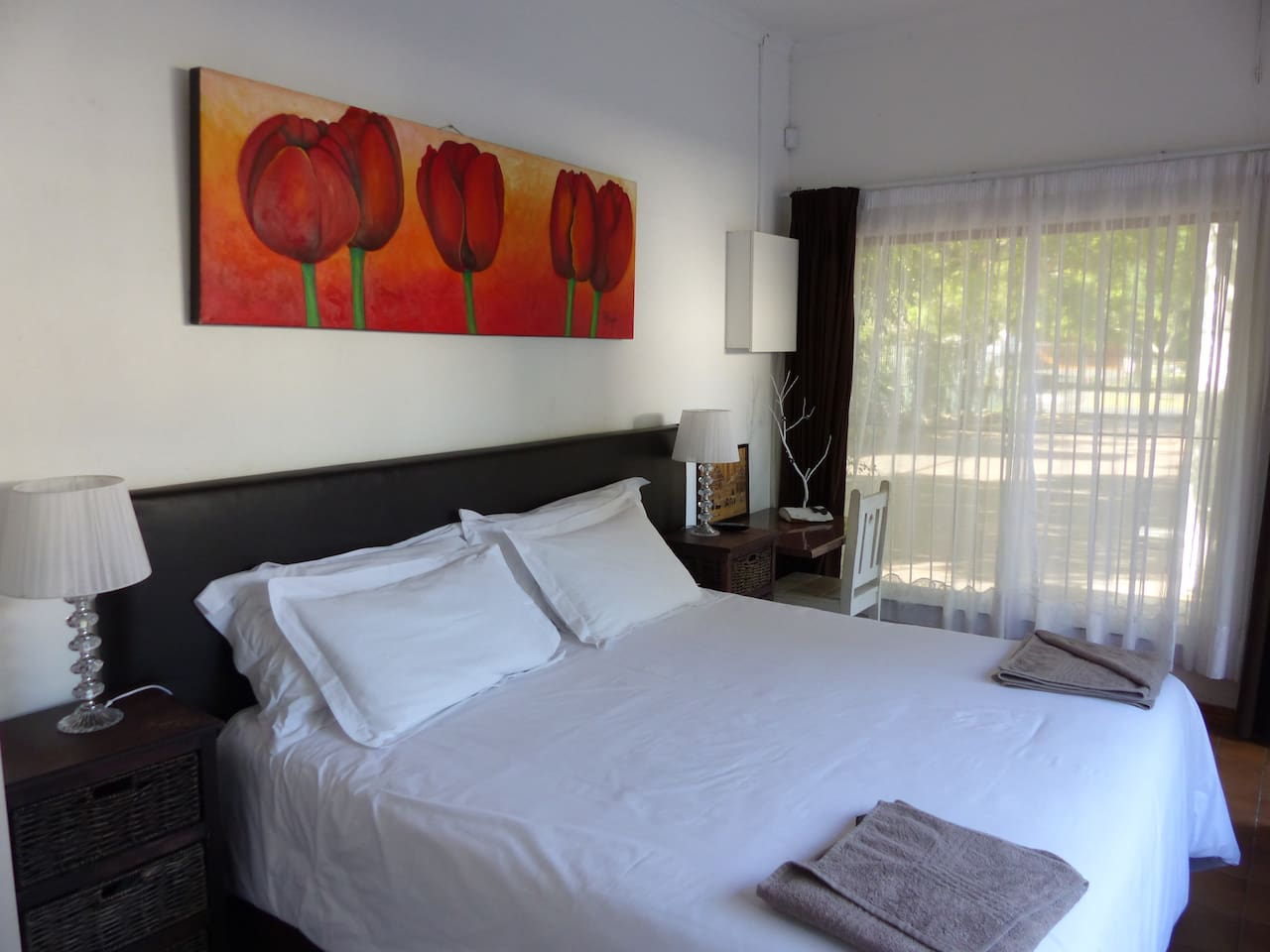 King Bed with hotel-quality linen, overlooking the parking area and the quiet street view