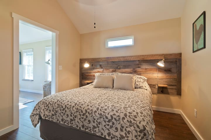 Reclaimed barnwood headboard and some natural light make a cozy and relaxing bedroom.