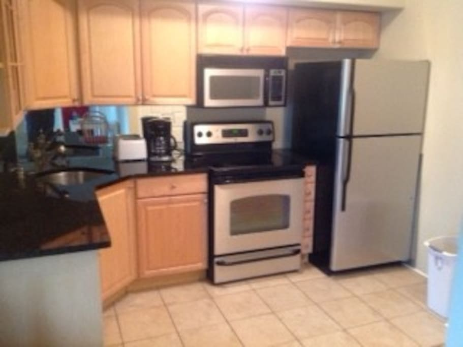 Modern kitchen with updated appliances, coffee maker, and enough dishes to cook a wonderful meal!