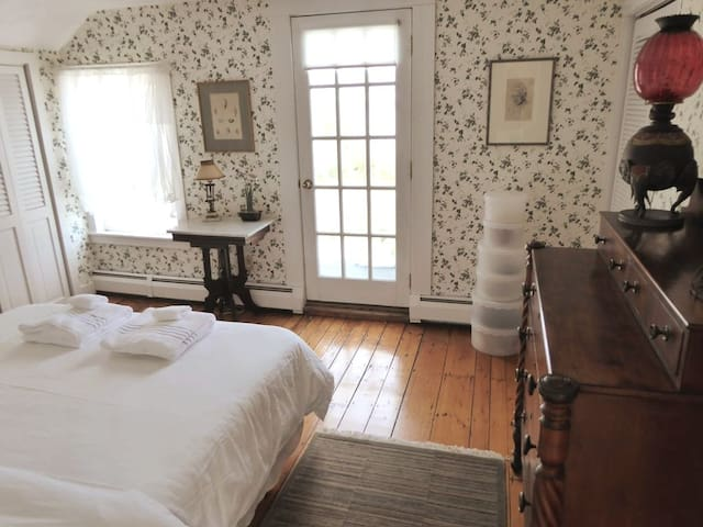 Bedroom one, which has a queen bed, a balcony with a water view, and ample closet space