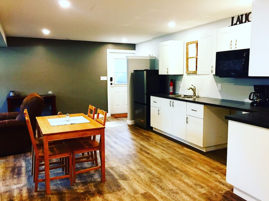 Open concept kitchen with fridge, coffee maker, counter top oven, induction hot plate, and all cooking accessories... pots, pans, tea towels, plates, glasses, cutlery, cooking utensils.