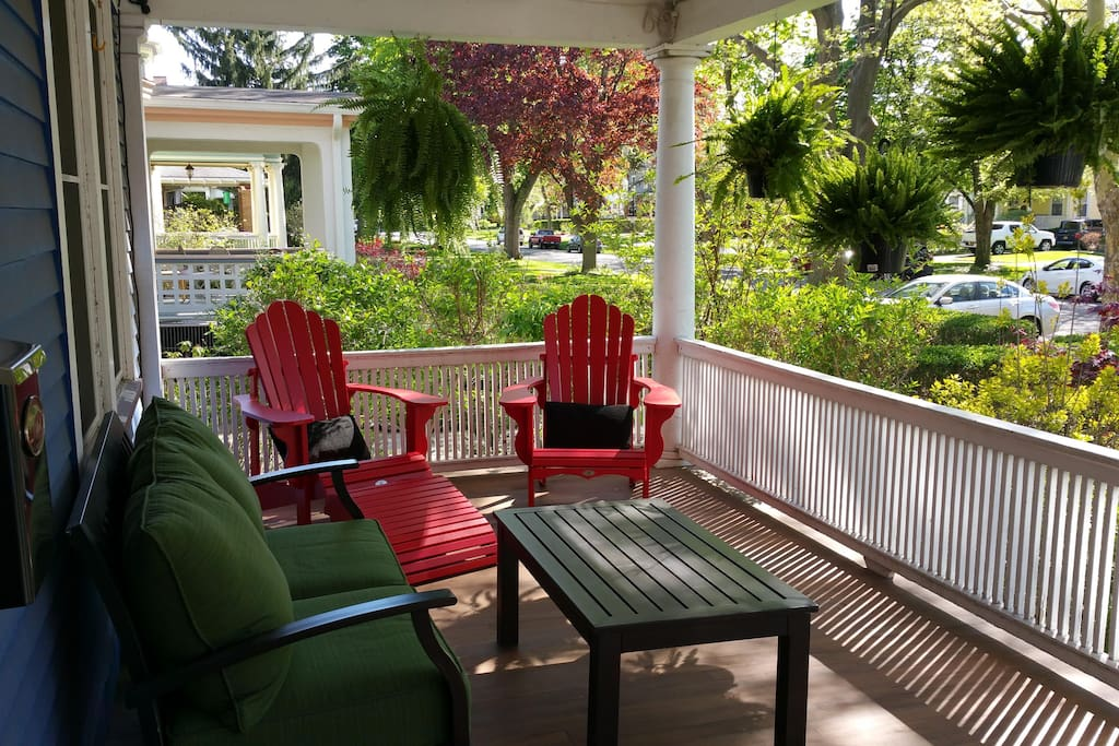 Guests enjoy time on the front porch.  The house is on a tree lined street.