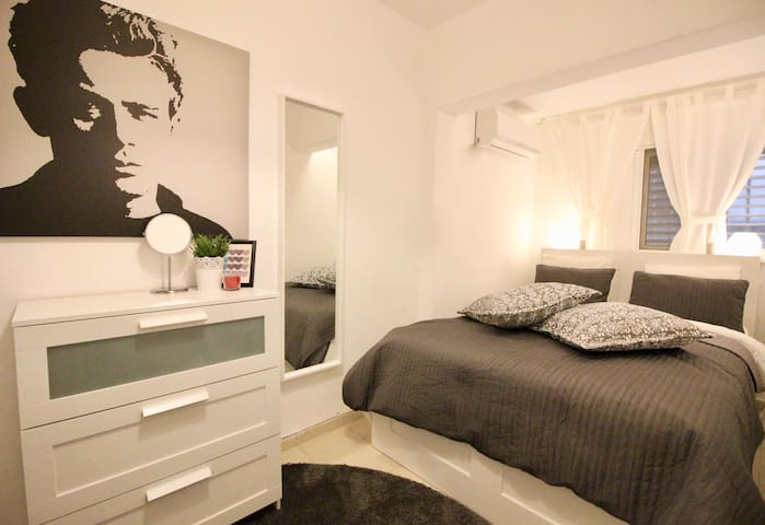 Bedroom with a Double  bed, air conditioner, mirror and drapes.