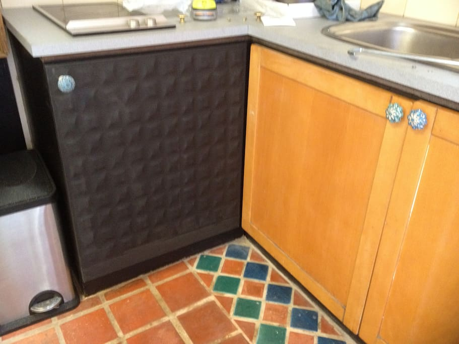 Kitchen cupboard contains microwave and little Pizza oven