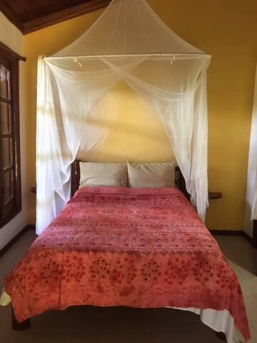 Suite 2 com varanda e vista para o jardim. Bedroom 2 with private bathroom and varanda.
