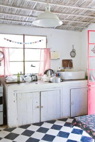 La cuisine équipée du nécessaire: four et cuisinière à gaz, évier, service de table et plats en tout genre, frigo et congélateur.