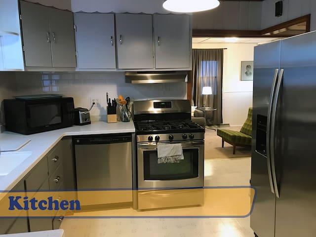 Kitchen with gas range, dishwasher, refrigerator with ice maker and all the dishes/utensils needed to prepare a meal.