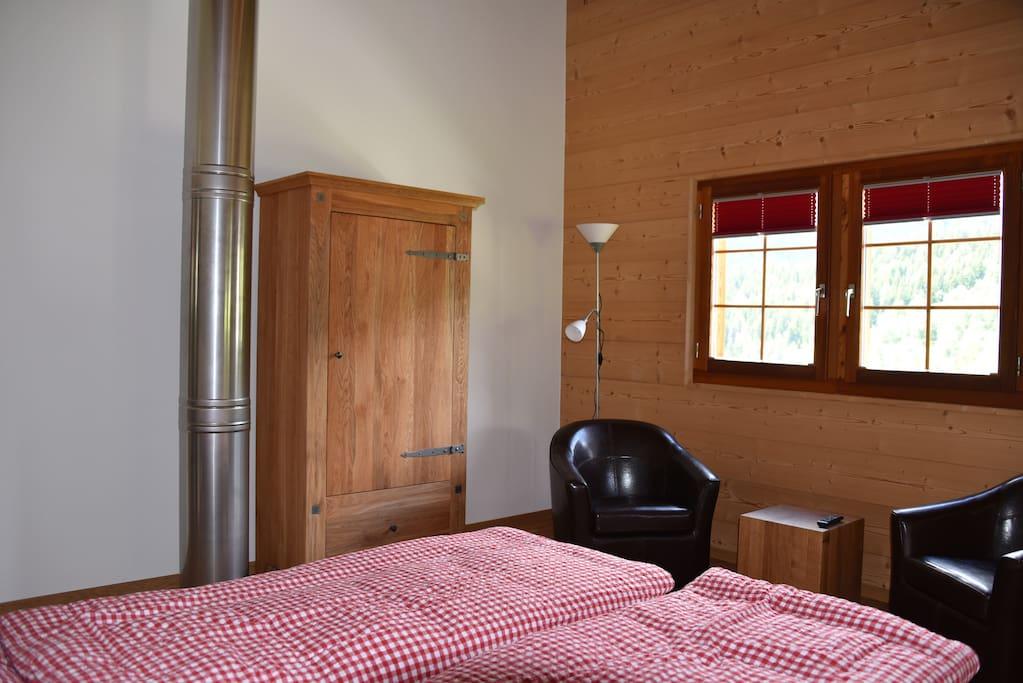 Ein Heizungsrohr für einen Schwedenofen  im unteren Stockwerk verläuft durch das Zimmer.