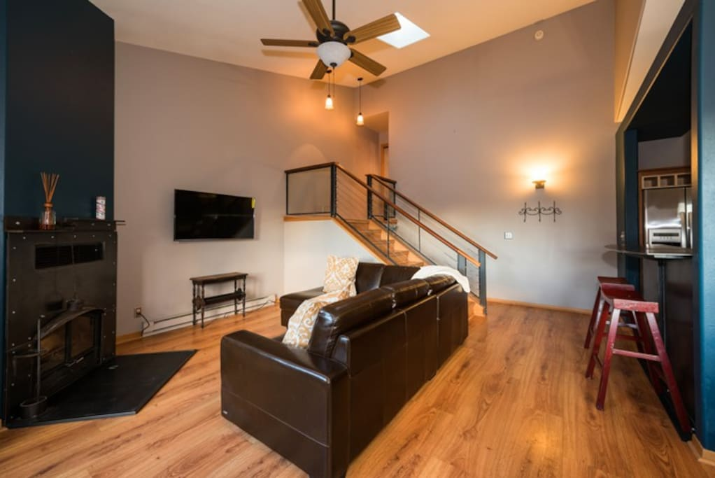 Living room on main level with TV, fireplace and balcony access.