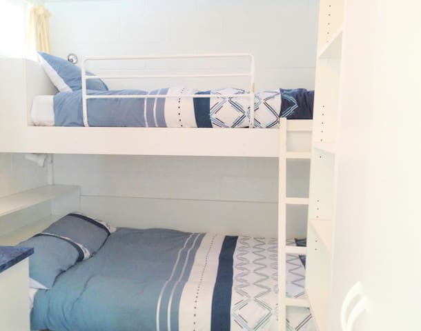 Bedroom with double bed below and single above.  Down doonas & ample storage