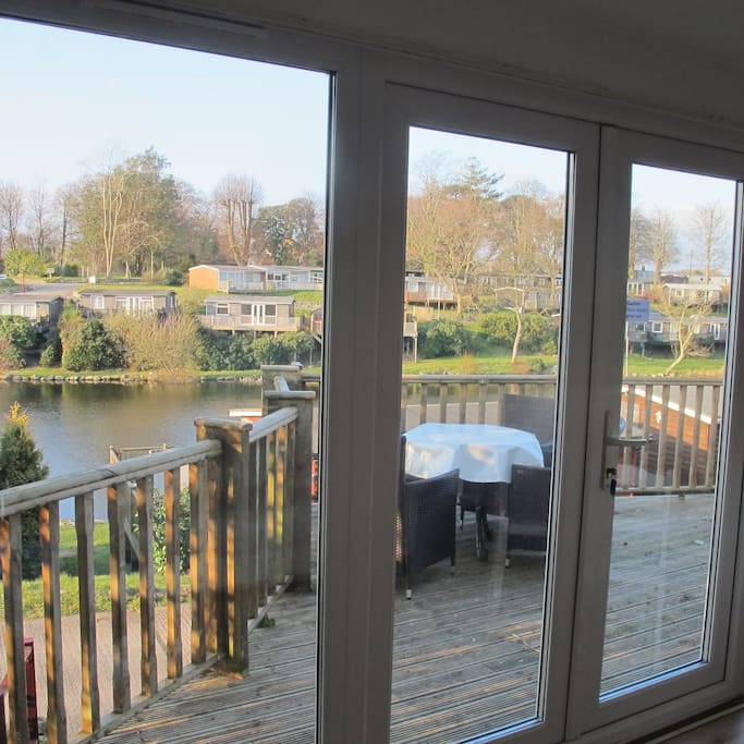View through patio doors onto the decking - lovely outside furniture over looking the lake