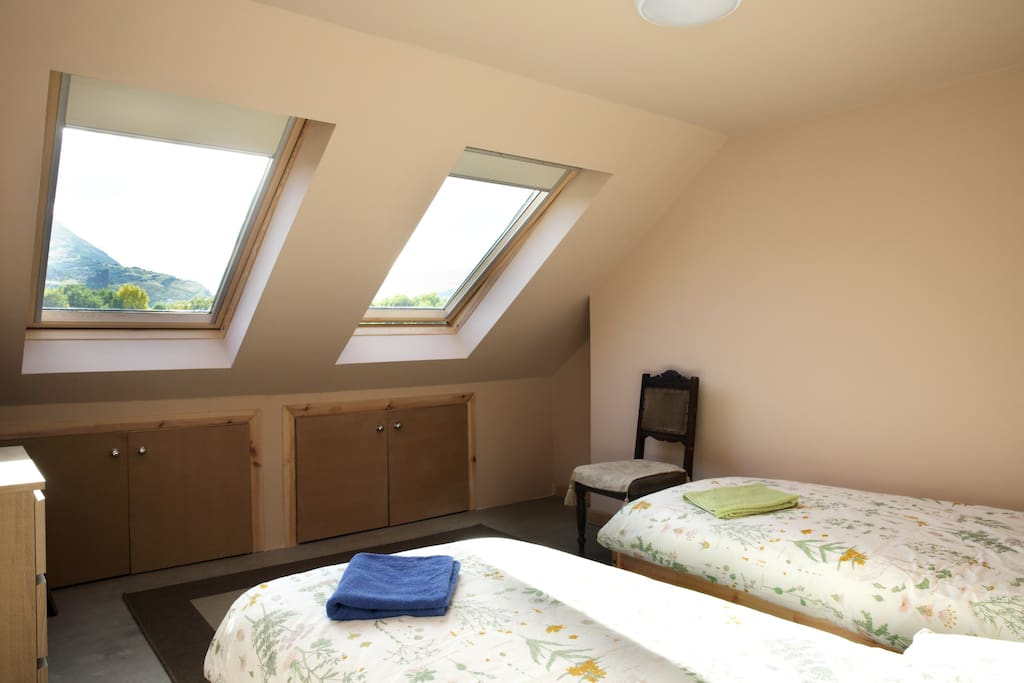 Front bedroom with large south-facing windows giving stunning views across Holyrood Park to Arthur's Seat