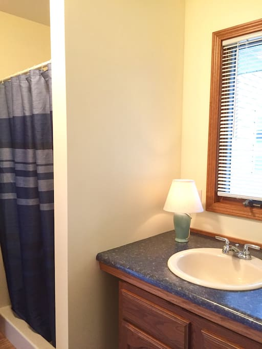 Full Bathroom off of kitchen. Shower is separate from bathroom/toilet area which is so nice when coming in off the beach or boating!
