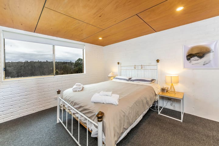 The bedroom is equipped with a queen sized bed, side tables and reading lamps, and has views out over the trees.